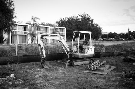 An excavator sits idle outside a derelict motel in Celebration, just outside of Orlando. In a state where Disney's Magic Kingdom exists just miles from urban slums, the collapse sheds strange subtropical light on the uneasy relationship between fantasy and reality. PHOTO: Neal Rockwell.