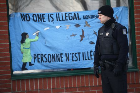 A cop appears impressed by the message that no one is illegal, outside the occupation of Quebec's Education Minister's office. Photo by Arij Riahi